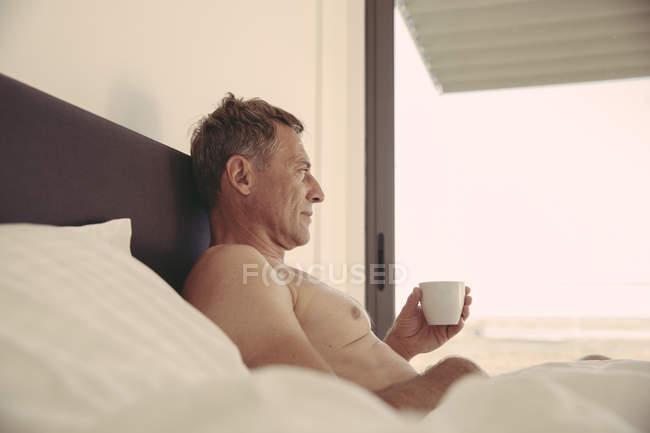 Homem relaxed na chávena de café da terra arrendada da cama — Fotografia de Stock
