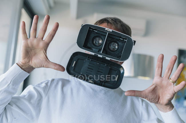 Confused man wearing VR glasses making a crazy face — Stock Photo
