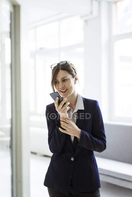 Businesswoman using cell phone in bright room — Stock Photo