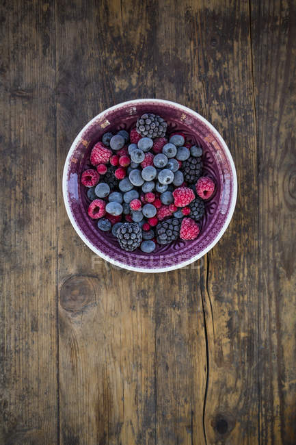 Bowl of deep frozen red currents, raspberries blueberries and blackberries on rustic wooden table — Stock Photo