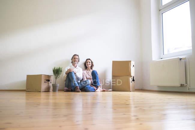 Coppia matura sorridente seduta sul pavimento in una stanza vuota accanto a scatole di cartone — Foto stock