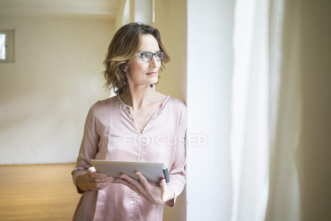 Reife Frau in leerem Raum halten Tablet am Fenster — Stockfoto