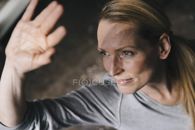 Woman shielding her eyes with her hand — Stockfoto