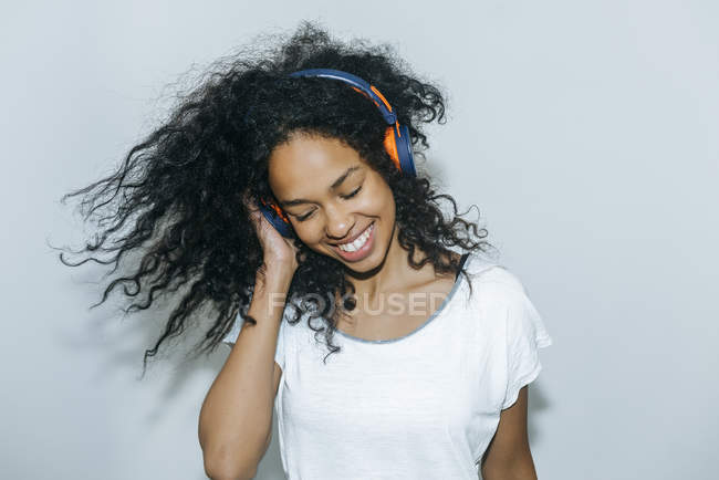 Portrait of happy young woman listening music with headphones — Stock Photo