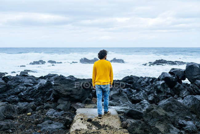 Azores, Sao Miguel, rear view of man looking at the sea from stony coast — Stock Photo