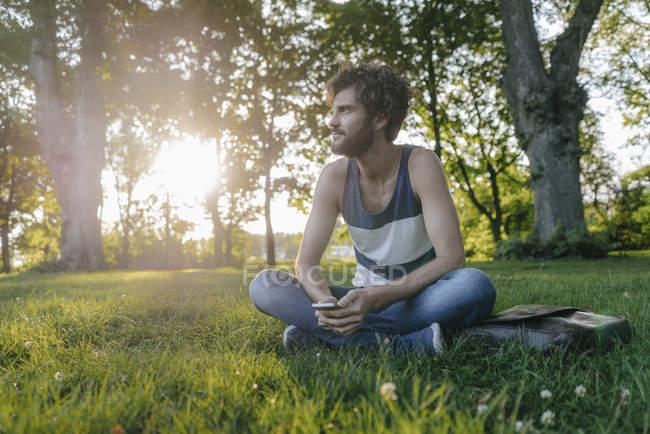 Человек сидит с сотовым телефоном в парке и смотрит в сторону — стоковое фото