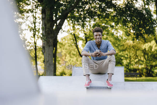 Smiling young african american man with cell phone sitting in skatepark — Fotografia de Stock