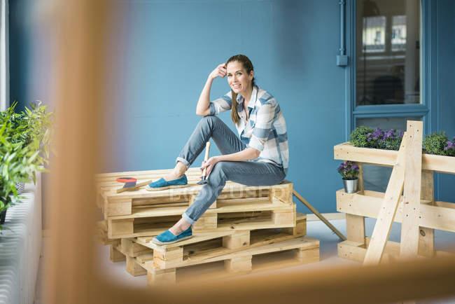 Bella donna ristrutturare la sua casa con pallet — Foto stock