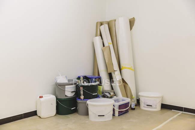 Матеріали для фарбування і обклеювання шпалерами в кутку кімнати — стокове фото