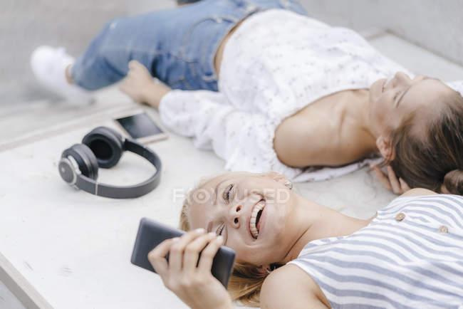 Due giovani donne felici con telefoni cellulari e cuffie nello skate park — Foto stock