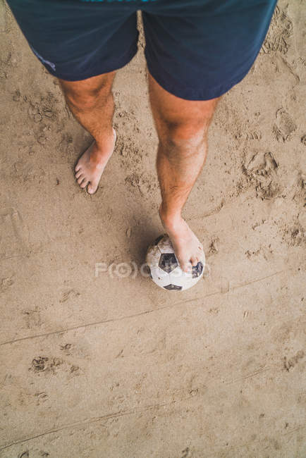 Low section of man with footall on the beach — Stock Photo