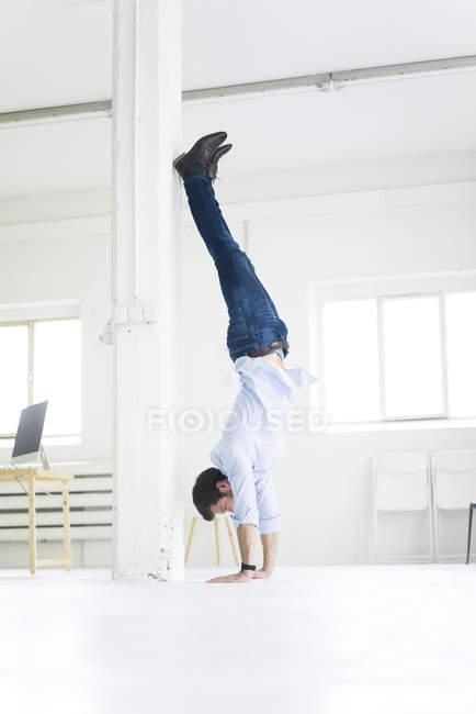 Бизнесмен делает стойку на руках в офисе — стоковое фото