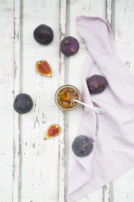 Vue du dessus des figues biologiques et verre de confiture de figues sur table en bois — Photo de stock