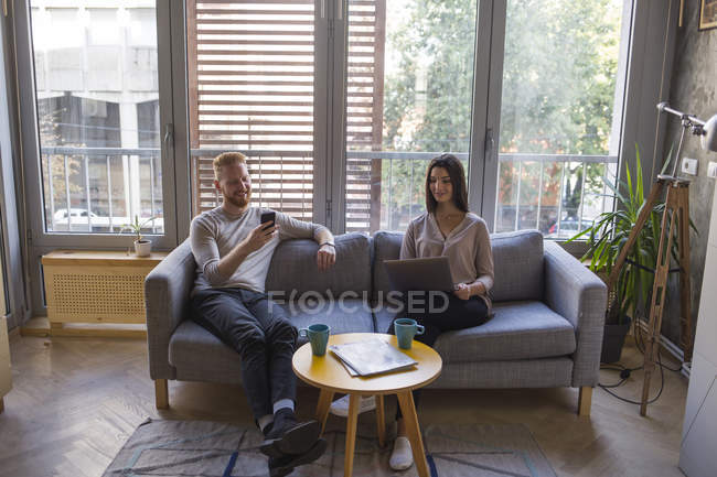 Couple sitting on couch with cell phone and laptop — Stock Photo