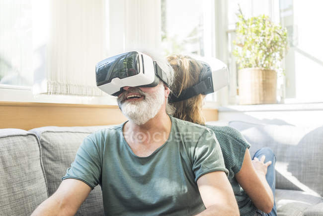 Happy mature couple sitting on couch at home wearing VR glasses — Stock Photo