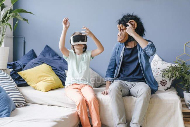 Отец в обезьяньей маске смотрит на сына в виртуальных очках дома — стоковое фото