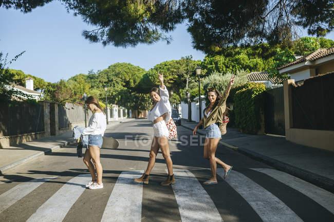 Tre amici che attraversano l'attraversamento pedonale mostrando il segno della vittoria — Foto stock