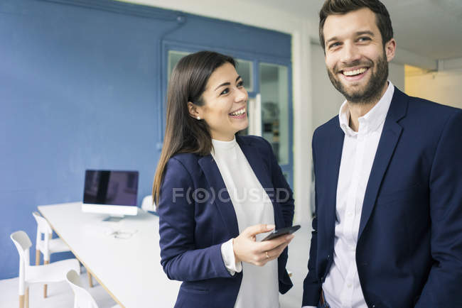 Happy businessman and businesswoman with cell phone in office — Stock Photo