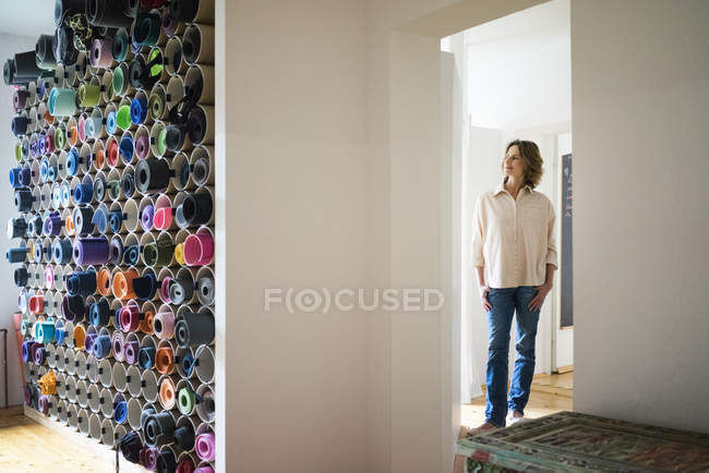 Mature woman standing in a room with assortment of yoga mats — Stockfoto