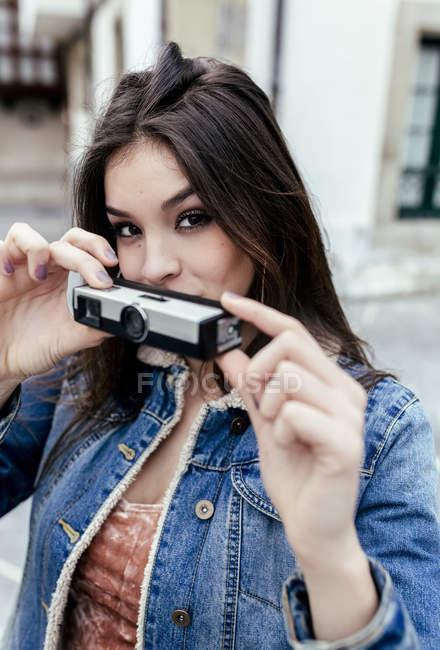 Retrato de uma mulher morena tirando uma foto com a velha câmera espiã — Fotografia de Stock