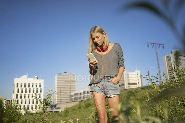 Young woman looking at cell phone — Stock Photo