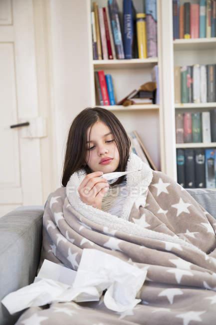 Niña enferma sentada en el sofá en casa mirando el termómetro clínico - foto de stock