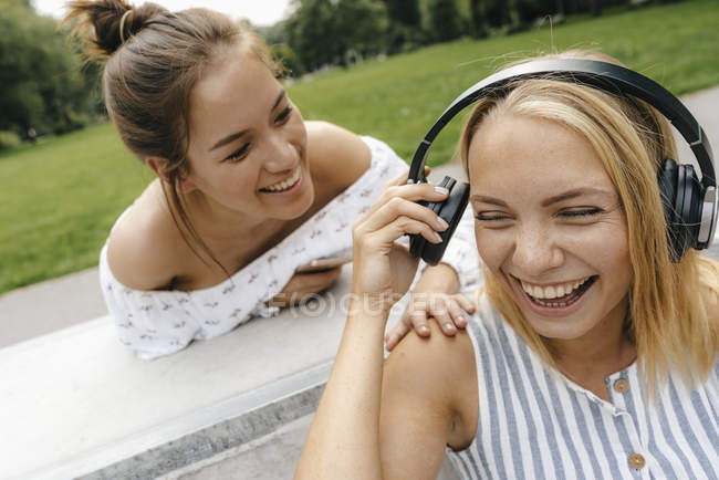 Two happy young women with headphones outdoors — Stock Photo
