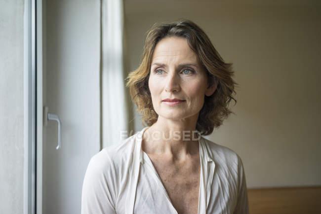 Porträt einer nachdenklichen reifen Frau am Fenster — Stockfoto