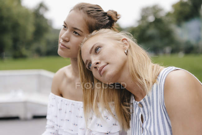 Young woman resting on female friend shoulder — Stock Photo