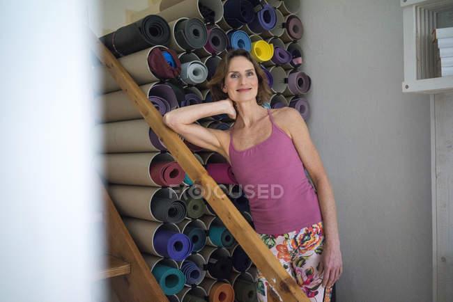 Porträt einer lächelnden reifen Frau, die neben einer Auswahl von Yogamatten steht — Stockfoto