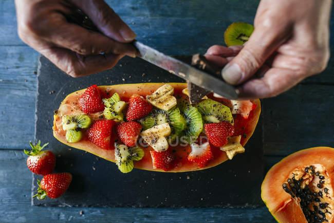 Primer plano de las manos del hombre cortando chocolate sobre media papaya adornada con trozos de plátano, kiwi y fresas - foto de stock