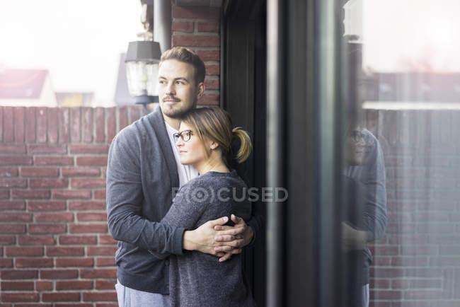 Пара обіймаючи на терасі будинку — стокове фото