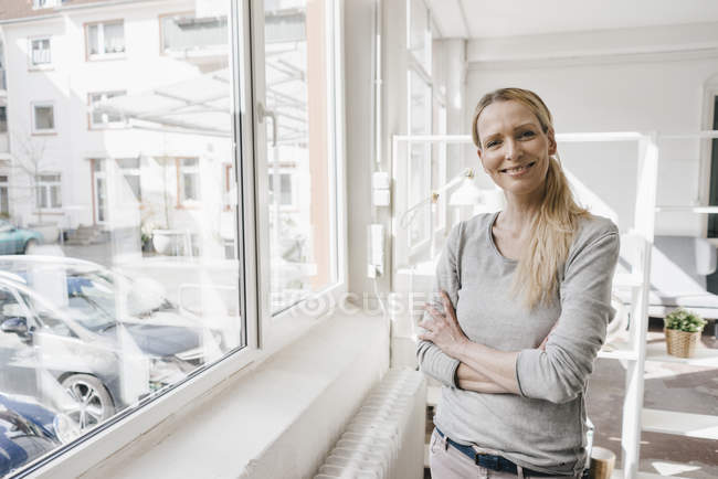 Portrait of smiling woman standing at the window — Stockfoto