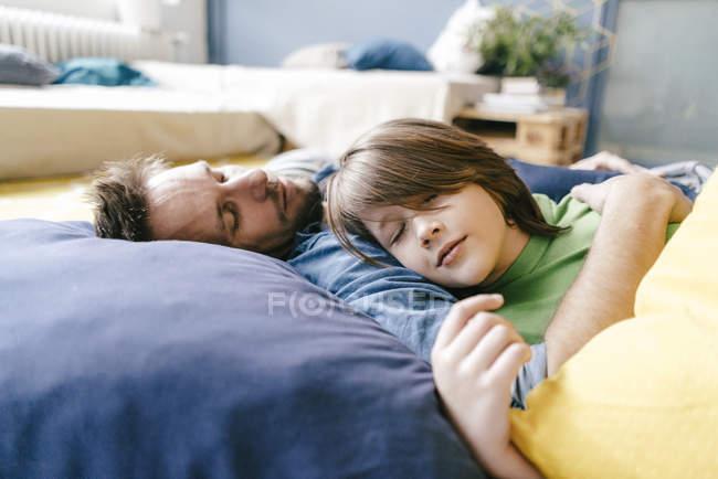 Отец и сын спят дома — стоковое фото