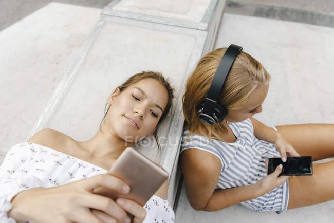 Due giovani donne con cellulari e cuffie nello skate park — Foto stock