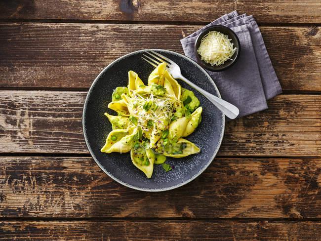 Паста з авокадо, паста Conchiglioni Rigati, соус з авокадо, м'ята, горох, червоний лук, Пармезан — стокове фото