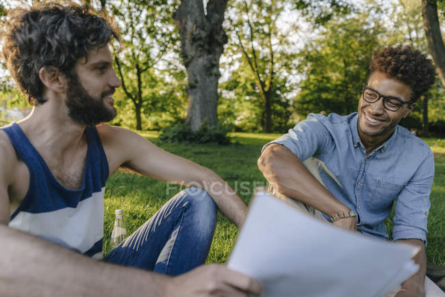 Two multicultural friends sitting in park and discussing papers — Stock Photo