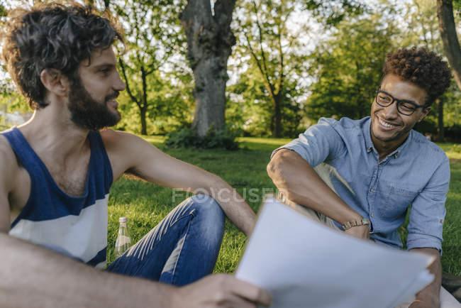 Два мультикультурных друга сидят в парке и обсуждают документы — стоковое фото