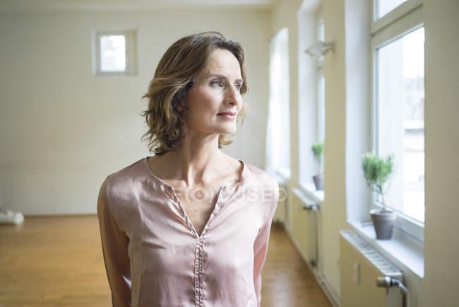 Nachdenkliche reife Frau im leeren Raum — Stockfoto