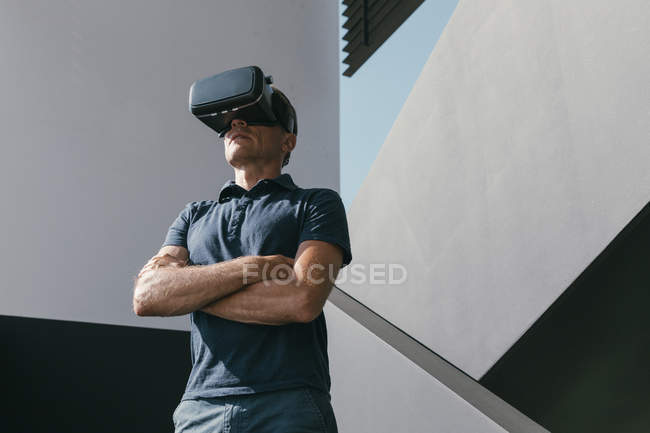 Mature man wearing VR glasses standing between walls of modern architecture — Stock Photo