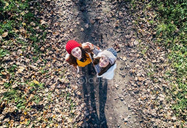 Duas mulheres felizes em pé em um caminho de floresta outonal — Fotografia de Stock