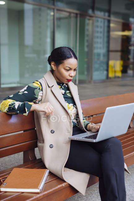 Empresária sentada no banco e usando laptop — Fotografia de Stock