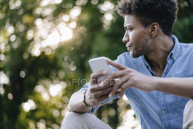 Hombre afroamericano joven con teléfono celular en el parque mirando hacia otro lado - foto de stock