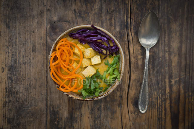 Turmeric curry dish with carrot, tofu, red cabbage and parsley in bowls — Stock Photo