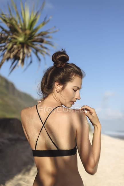 Задній вид привабливою молодої жінки на пляжі — стокове фото