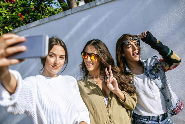 Trois jeunes femmes souriantes prenant selfie avec smartphone — Photo de stock