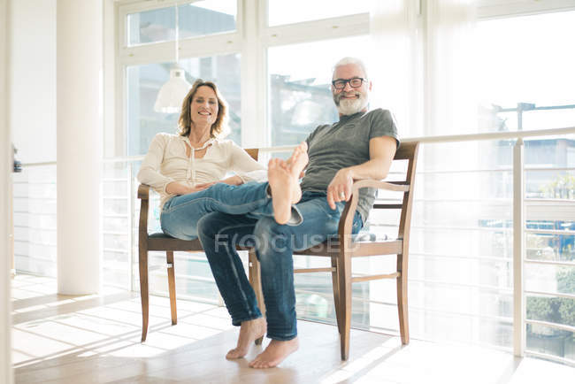 Portrait of relaxed mature couple sitting on chairs at home — Stockfoto