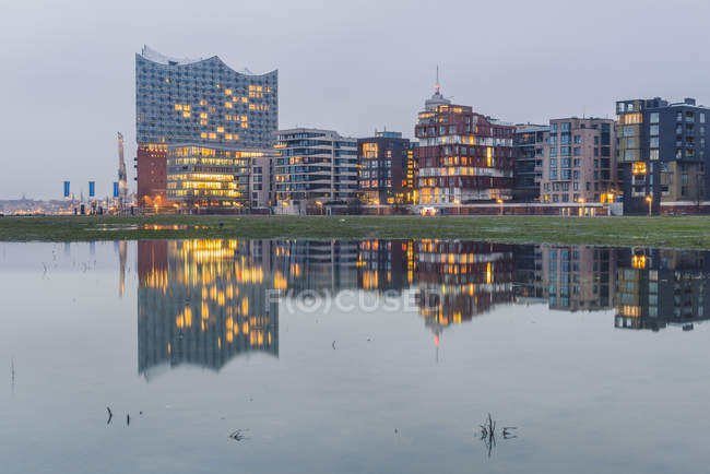 Germany, Hamburg, Hafencity, modern buildings and Elbe Philharmonic Hall in the evening — Stock Photo