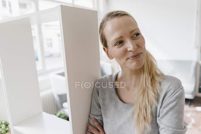 Lächelnde Frau lehnt sich an ein Regal — Stockfoto