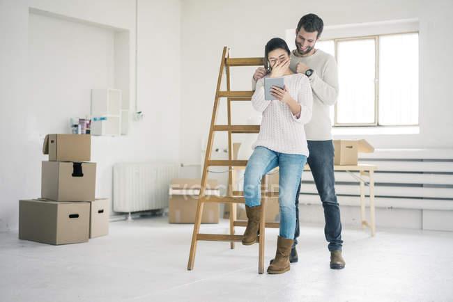 Сміється пара на сходах в новому будинку, дивлячись на планшеті — стокове фото